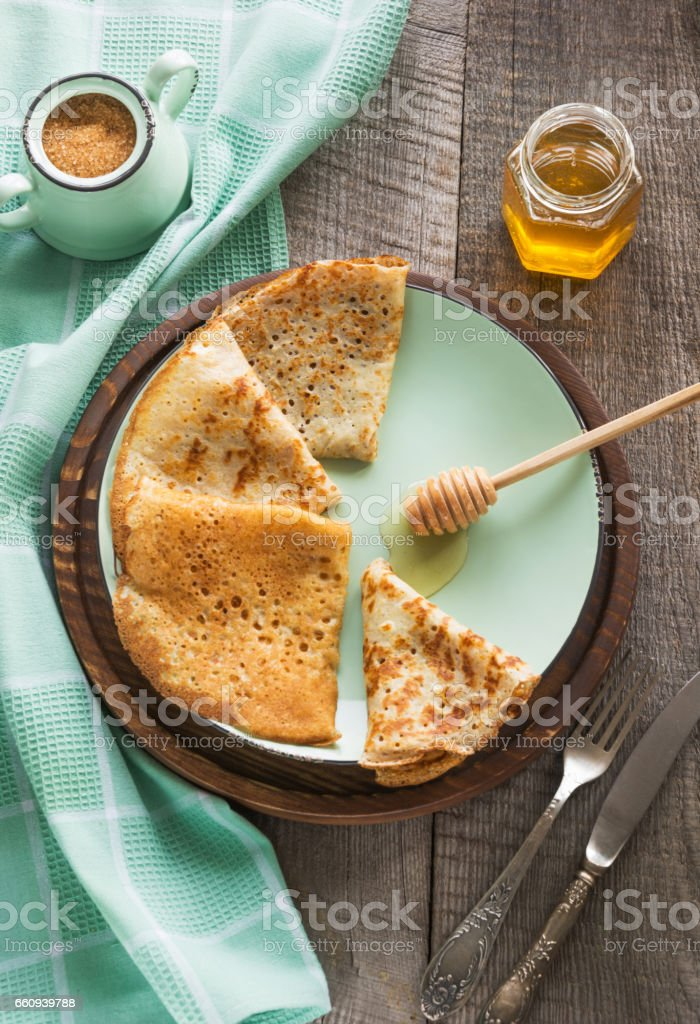 Tasty traditional russian breakfast of slapjack with honey on plate. Rustic style. Space for your text. stock photo