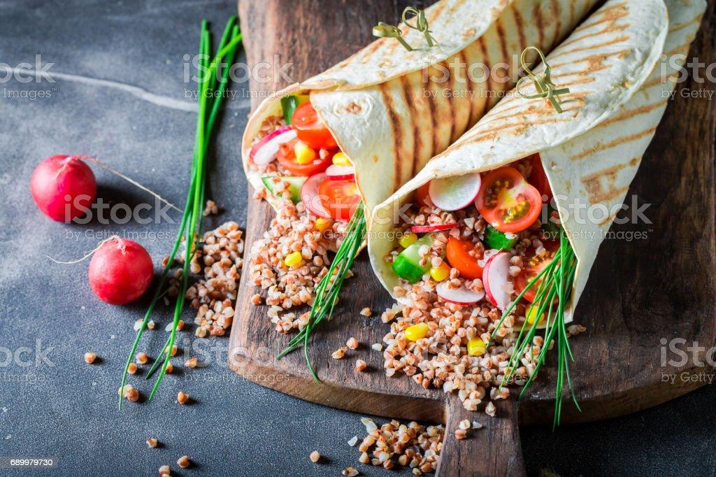 Tasty vegetarian tortilla with groats, cherry tomatoes and radish stock photo