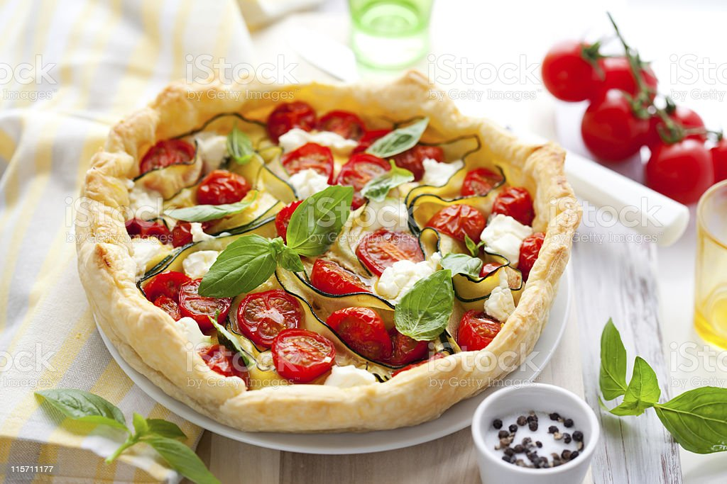 A tasty zucchini tomato and onion quiche stock photo
