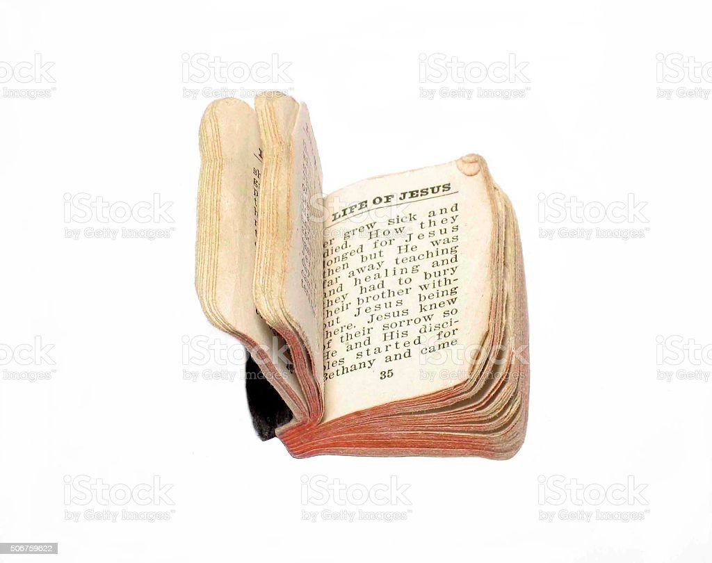 Tattered and torn miniature bible on white photo. stock photo