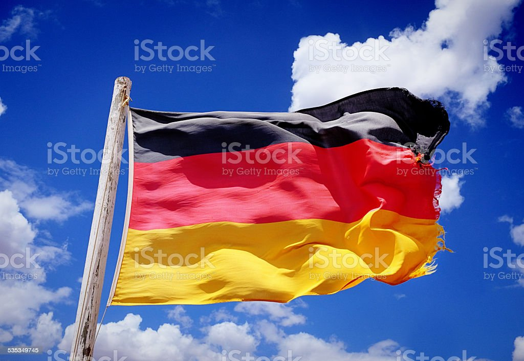 Tattered German national flag blowing in the breeze stock photo