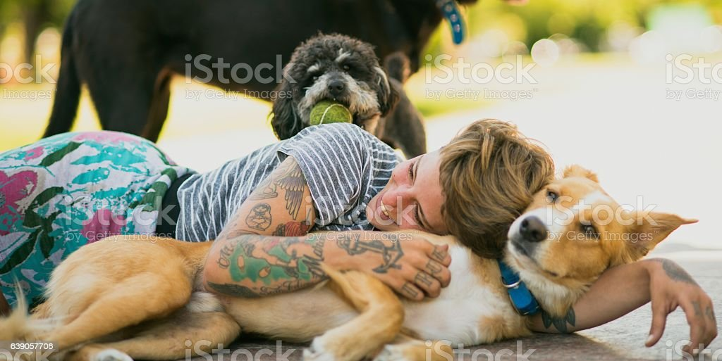 Tattoed woman relaxing with dogs stock photo