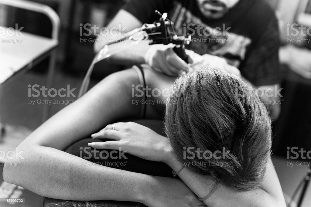 Tattoo artist at work stock photo