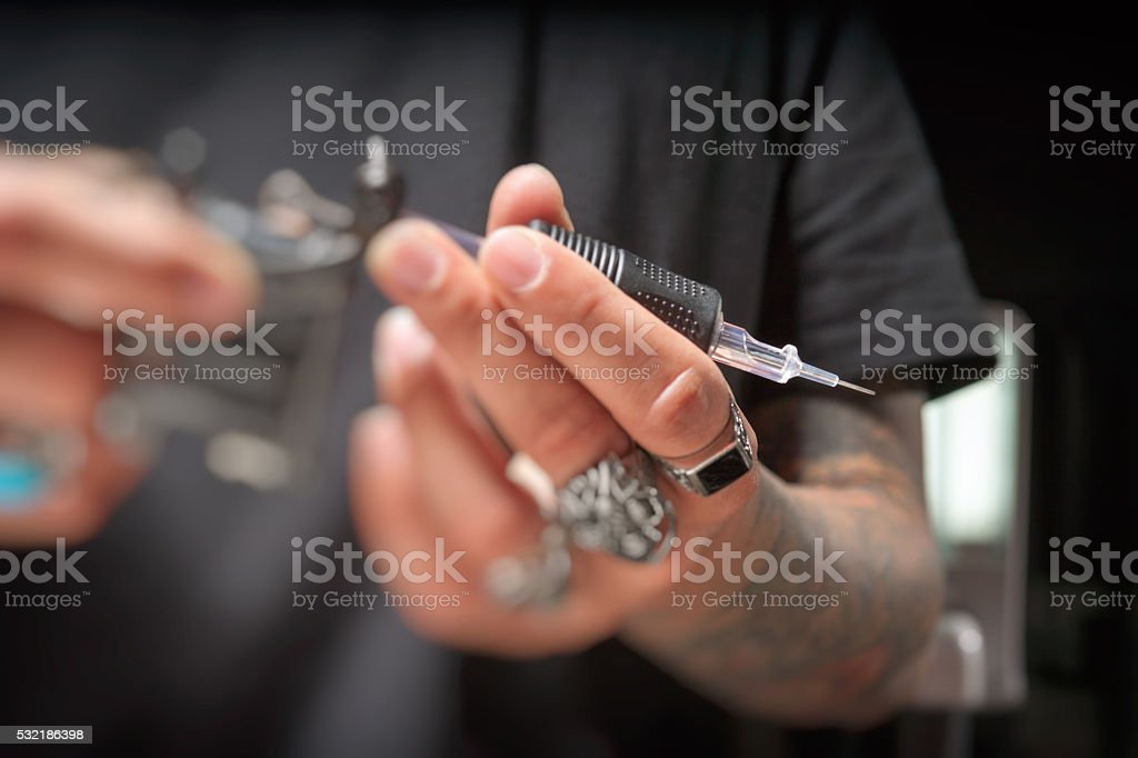 Tattoo artist holding tattoo gun with needle attached stock photo
