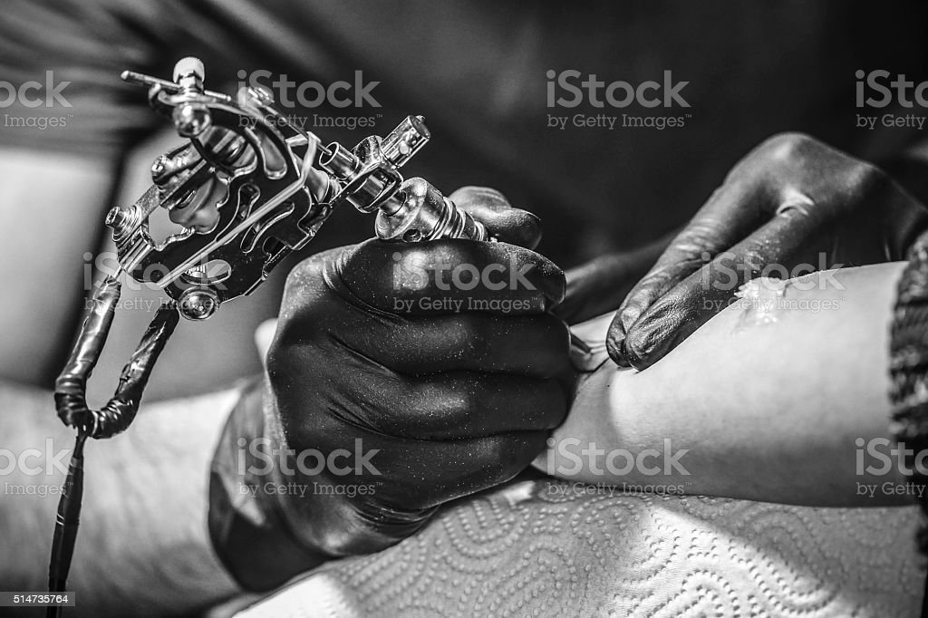 Tattoo artist working stock photo