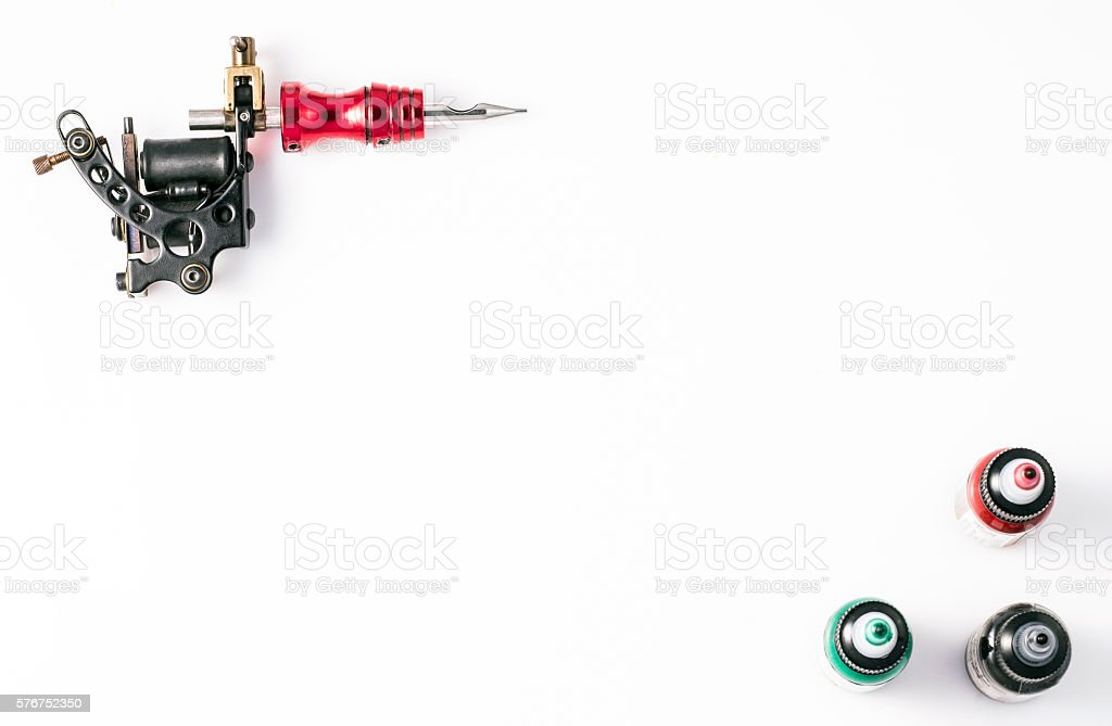 Tattoo machine and three bottles of ink stock photo