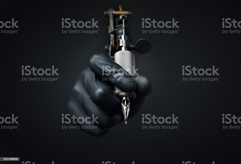 Tattoo machine dark background stock photo