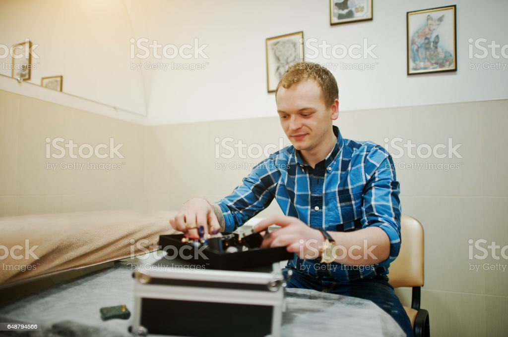 Tattoo master at his saloon with his tattoo devices stock photo