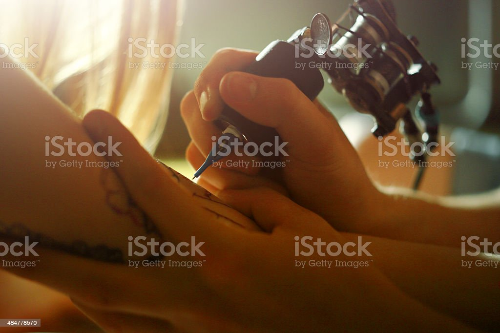 Tattoo master tattooing on the a girl arm. stock photo