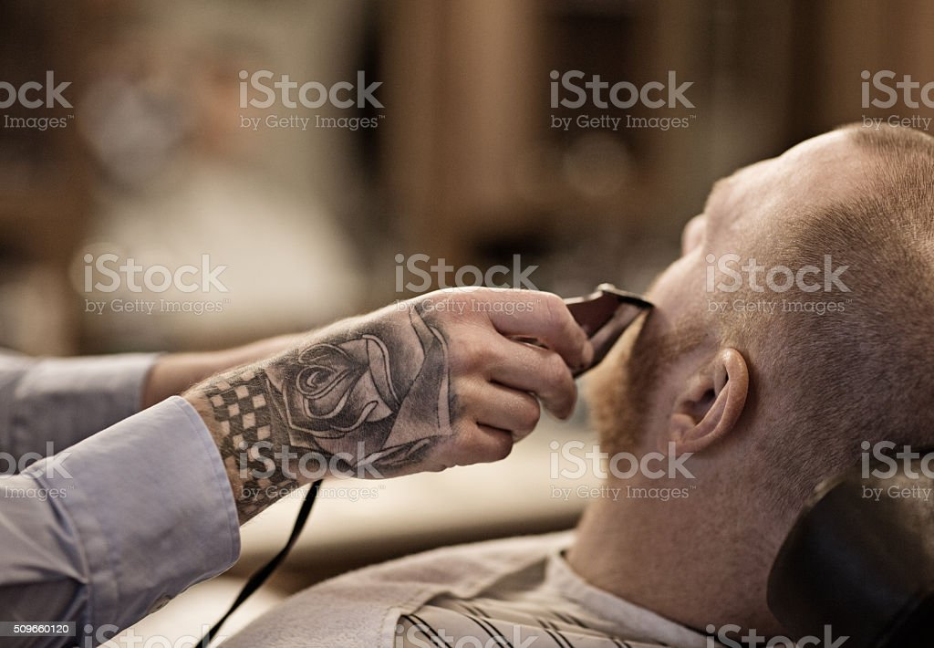 Tattooed barber with a bearded bald male client stock photo