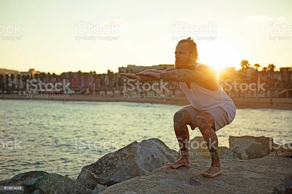 Tattooed bearded handsome male stretching before a evening seafront workout stock photo