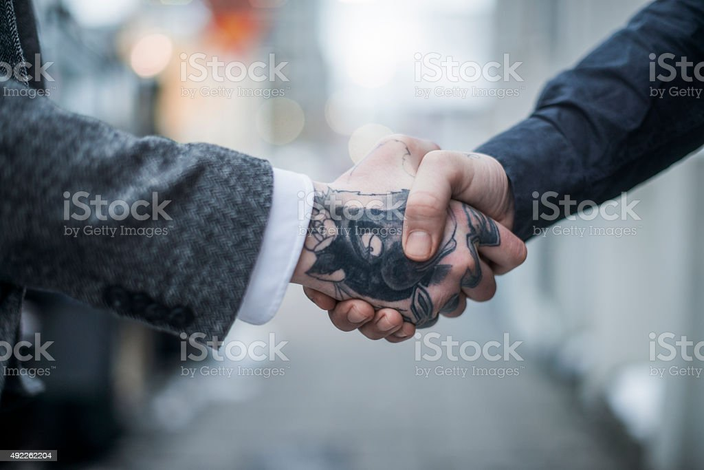 Tattooed businessman greeting colleague outdoors stock photo