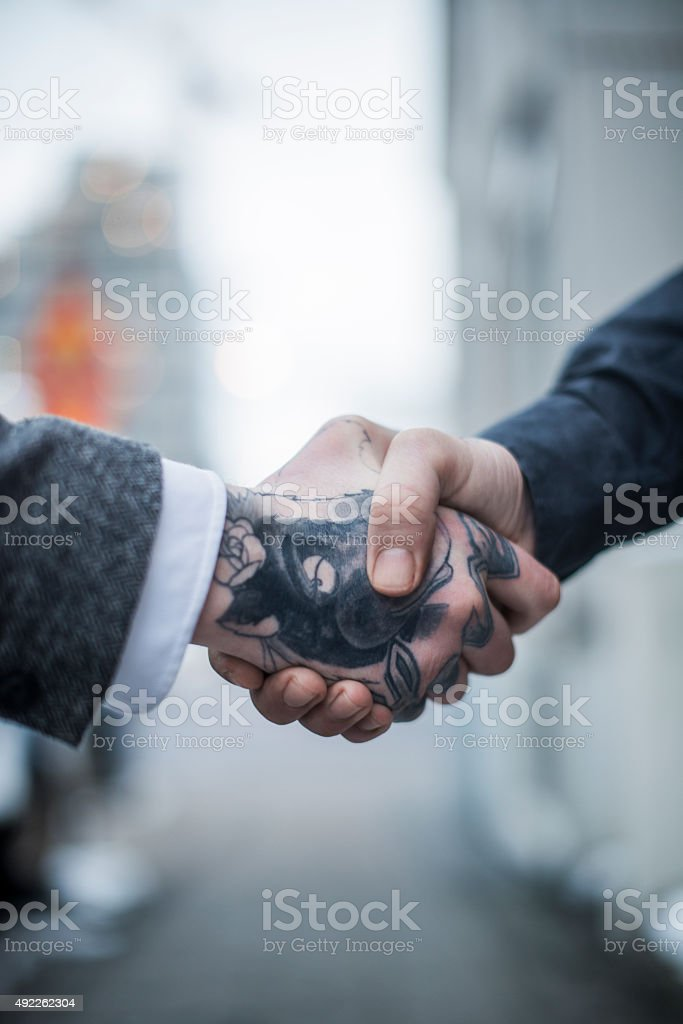 Tattooed businessman shaking hand with colleague stock photo