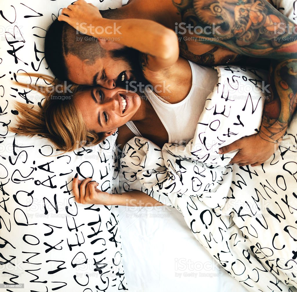 Tattooed Couple Flirting In Bed. stock photo