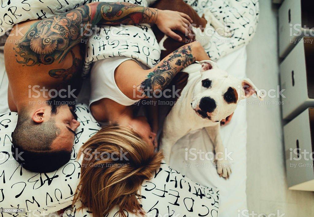 Tattooed Couple With Their Dog Sleeping stock photo