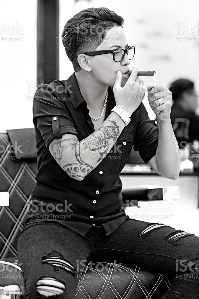 Tattooed female barber smoking in barber shop stock photo