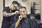 Tattooed female barber working on smoking client in barber shop
