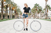 Tattooed Girl Standing behind a Bicycle