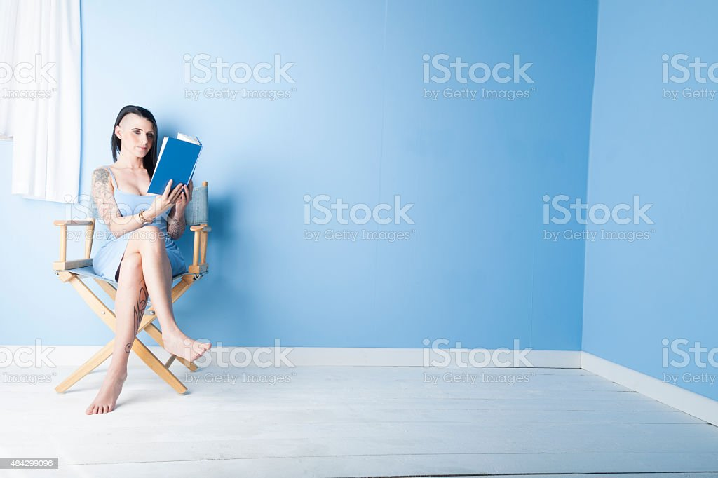 Tattooed Girl Wearing A Pastel Blue Dress Reading Her Book stock photo
