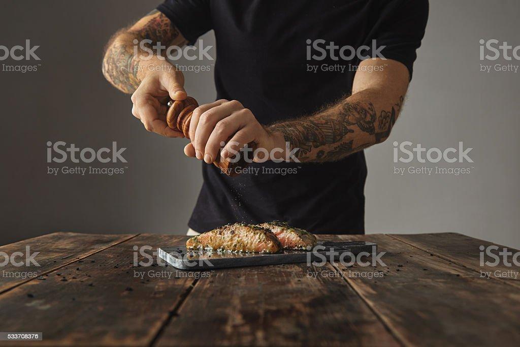 Tattooed man cooks grilled salmon process stock photo