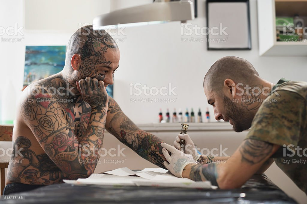 Tattooed man getting a new tattoo on his arm. stock photo