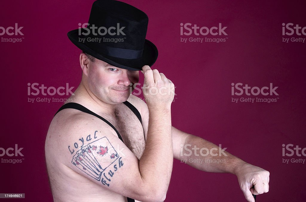 Tattooed man in suspenders touching top hat. royalty-free stock photo