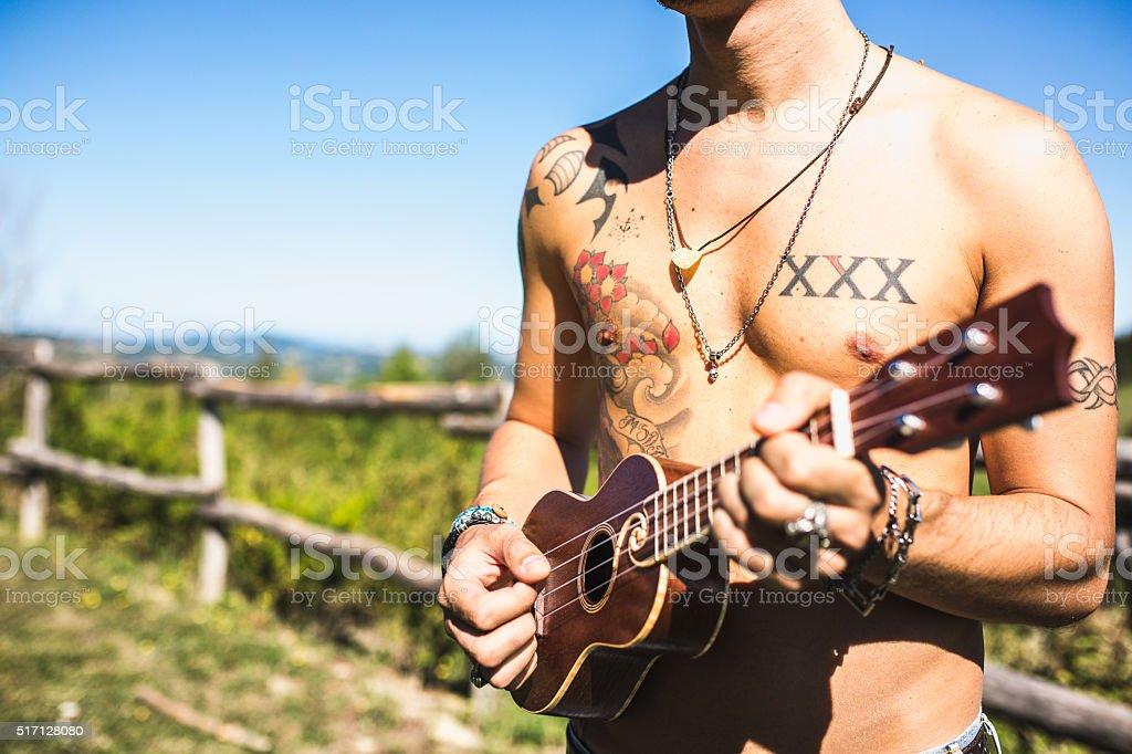 Tattooed man playing ukulele stock photo