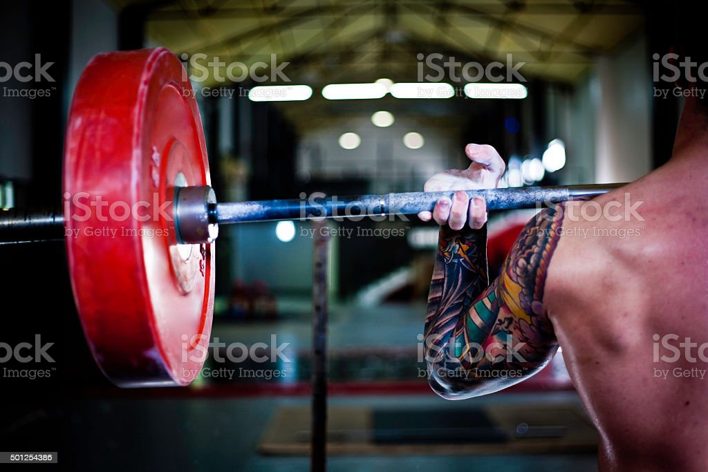 tattooed man practising weightlifting in a gym gym stock photo