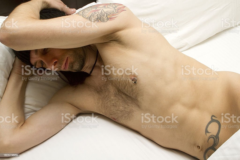 Tattooed Man's Body Under The Sheets stock photo