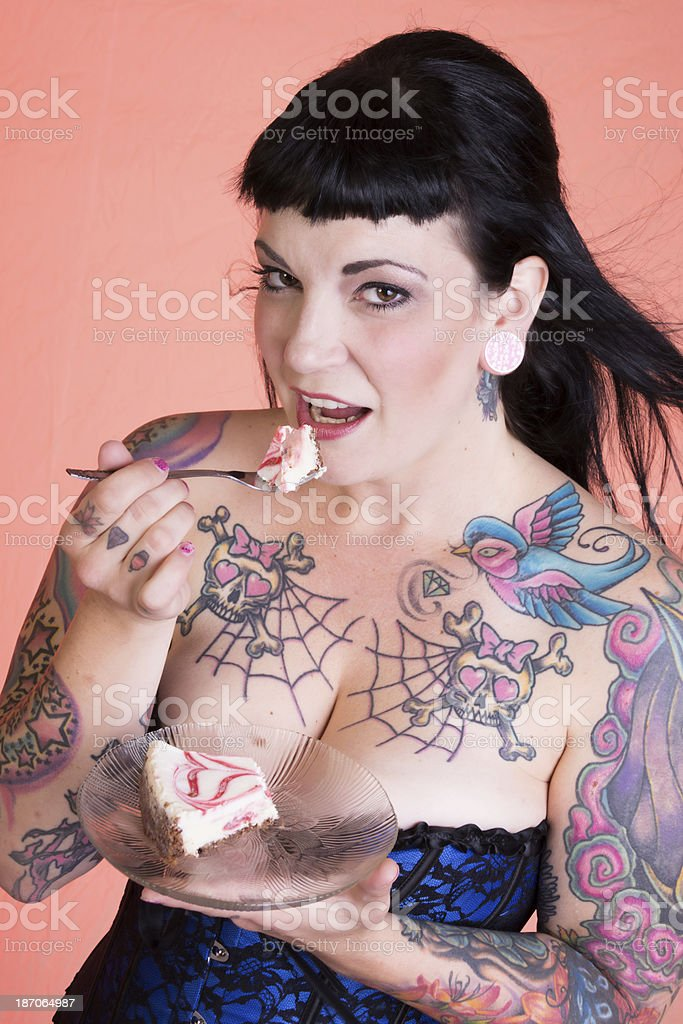 Tattooed pinup model looking at camera, about to eat cheesecake. royalty-free stock photo