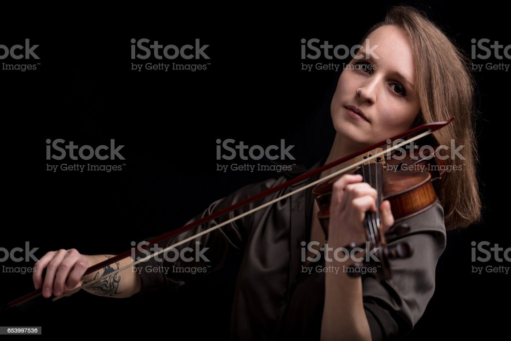 tattooed violinist woman playing in black background stock photo