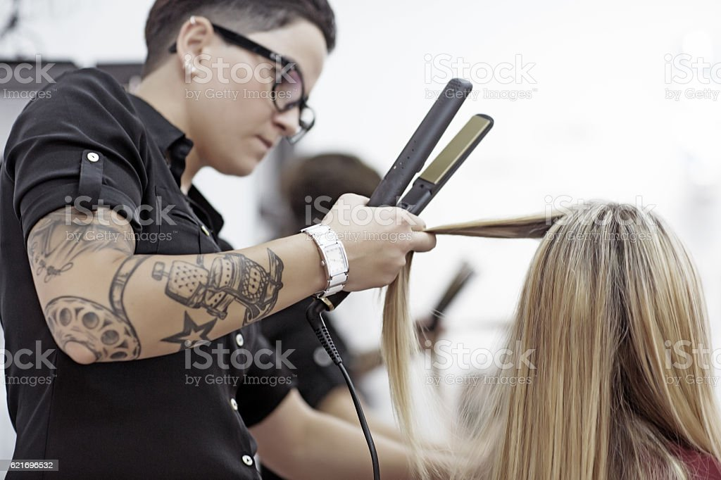 Tattooed woman hairstylist working on blonde woman client stock photo