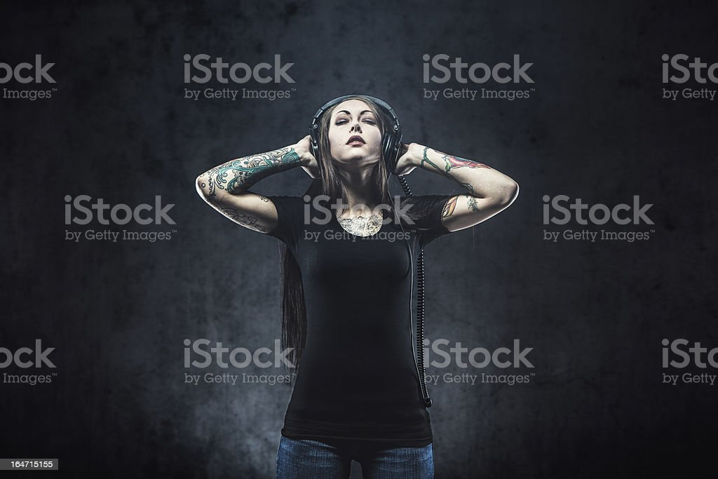 Tattooed Woman Listening to Music royalty-free stock photo