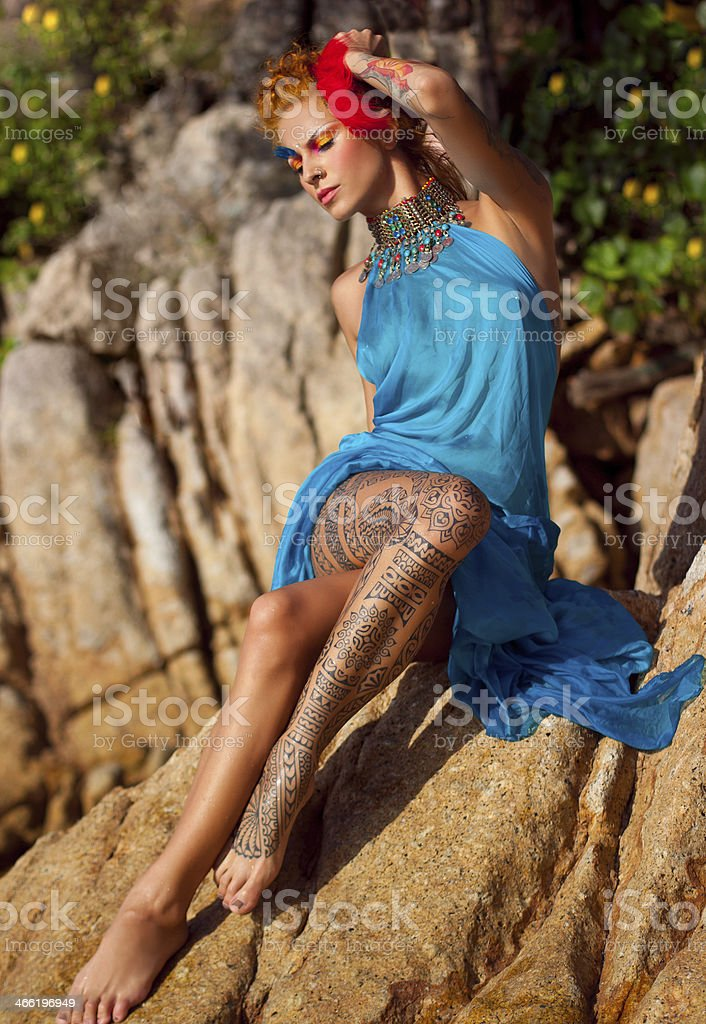 Tattooed woman on the rocks stock photo
