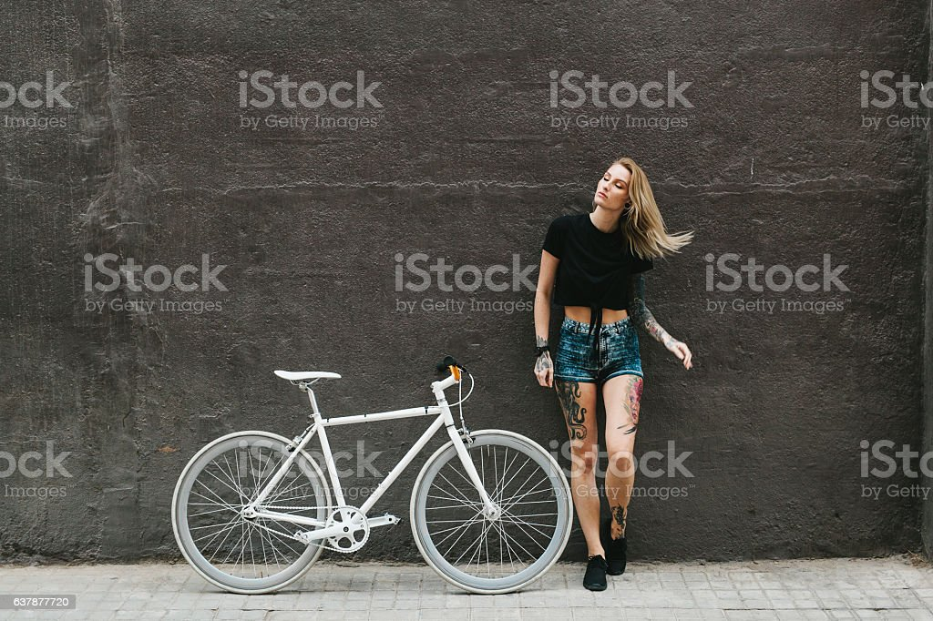 Tattooed Woman with a White Bicycle Leaning on Dark Wall stock photo