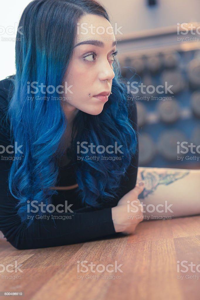 tattooed woman with blue hair exercising in gym pole dance stock photo