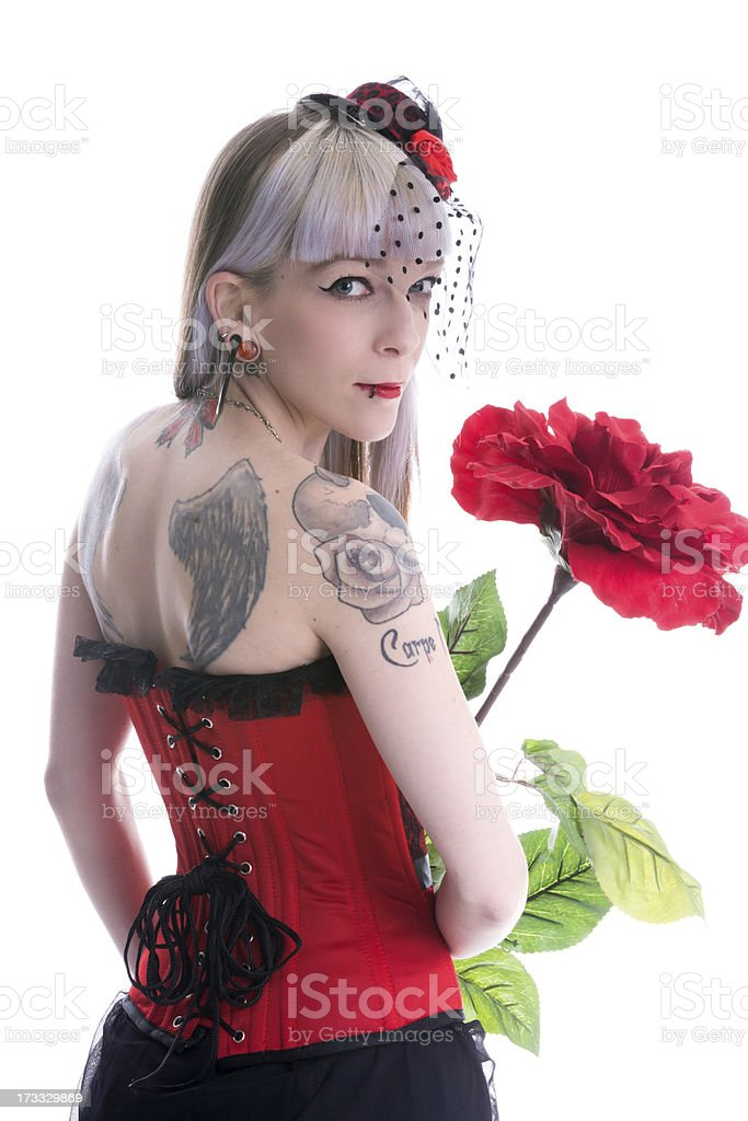 Tattooed woman with large rose looking back over shoulder. royalty-free stock photo