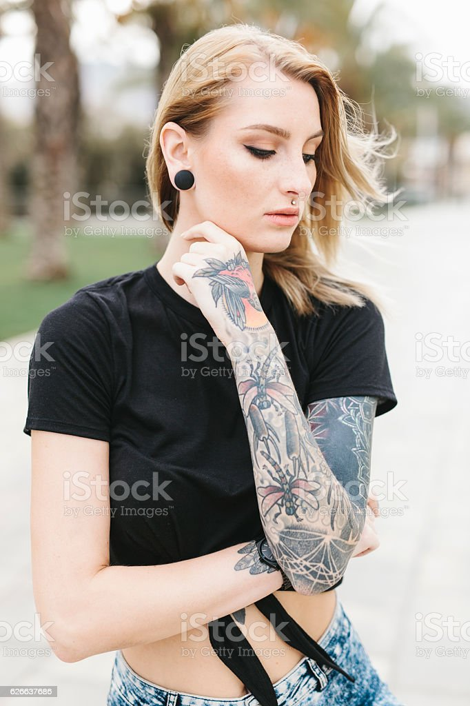 Tattooed Woman with Wind Brushing through Her Hair stock photo