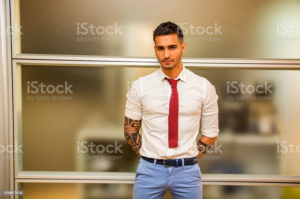 Tattooed young male office worker standing stock photo