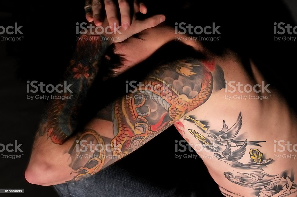 Tattooed youth holding head in his hands royalty-free stock photo