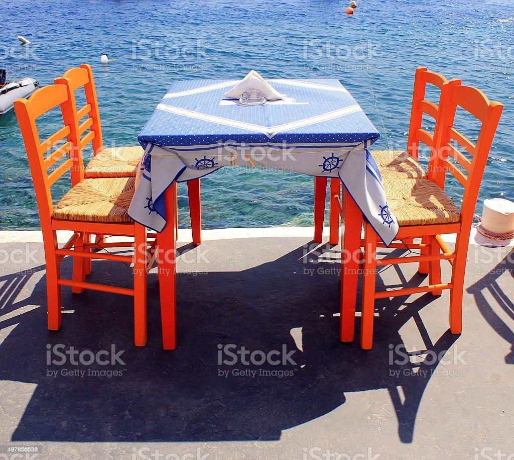 tavern with orange wooden chairs by the sea coast, Santorini stock photo