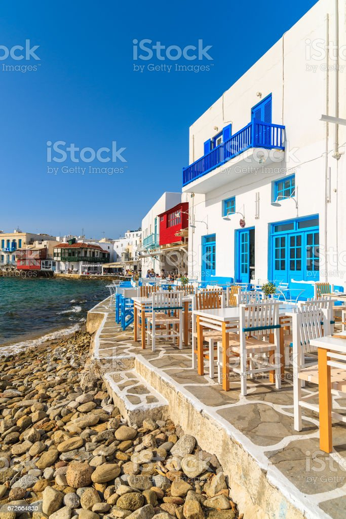 Taverna tables on coastal promenade along beach in Little Venice part of Mykonos town, Mykonos island, Greece stock photo