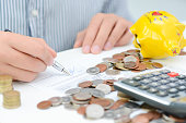 Tax calculation or new loan agreement with calculator and coins