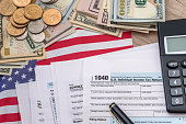 tax concept - 1040 tax form, pen, us money and