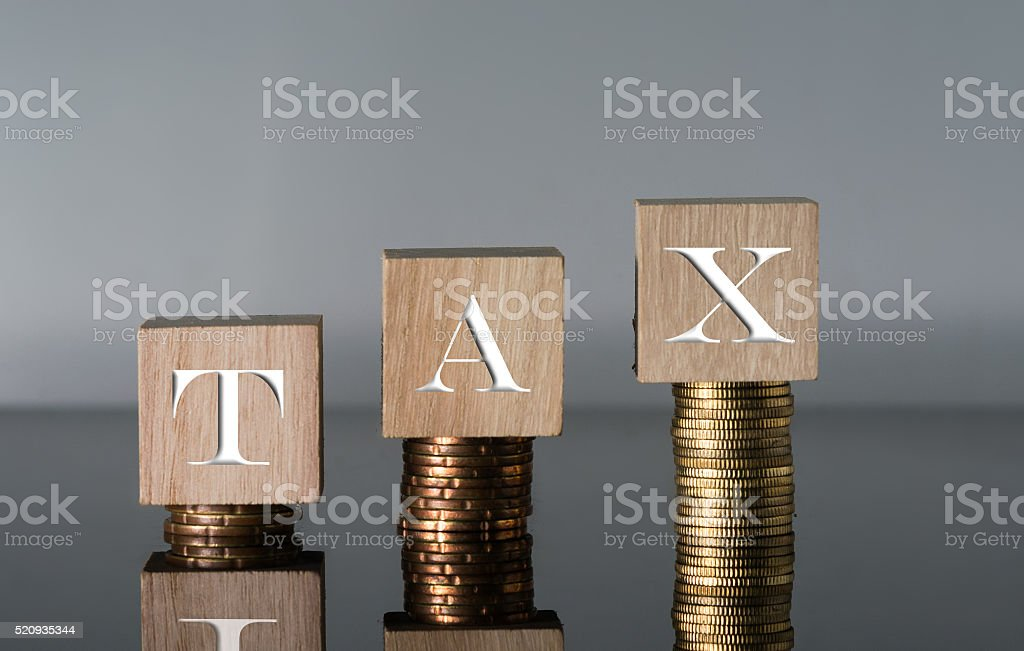 Tax Concept with wooden block on stacked coins stock photo