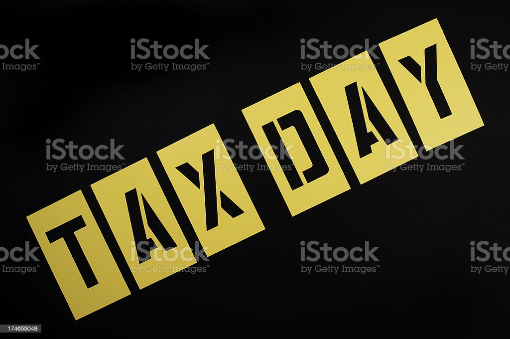 Tax Day Message in Yellow Stencil on Black stock photo