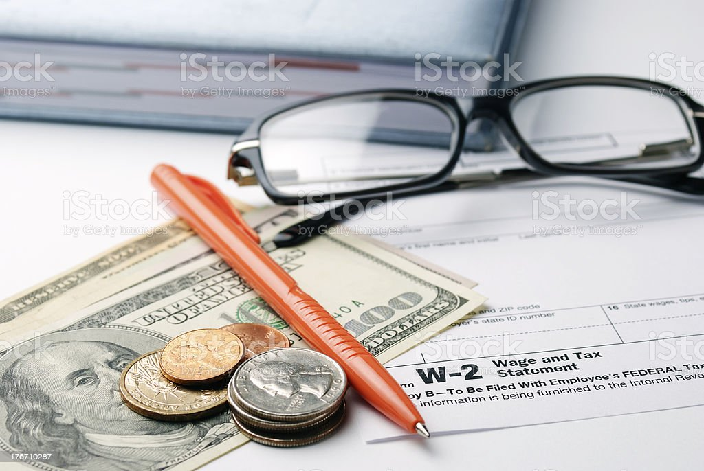 Tax document underneath spectacles coins and pen stock photo