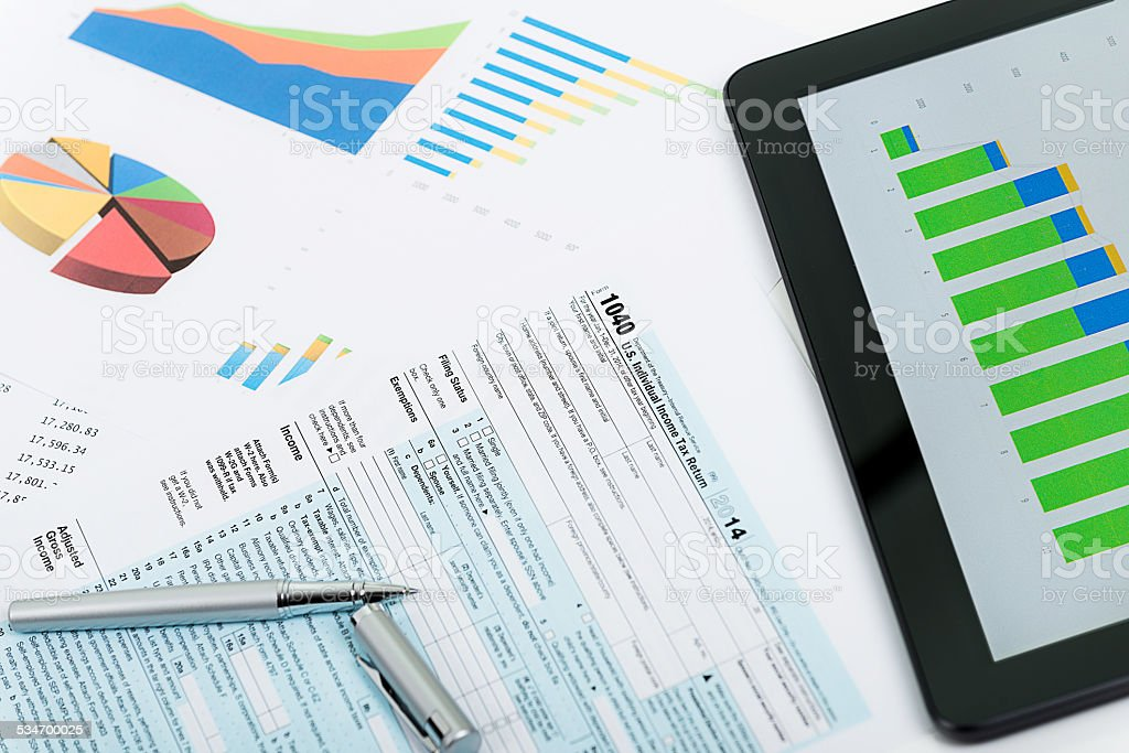 Tax form 1040, charts and financial data on office desk stock photo