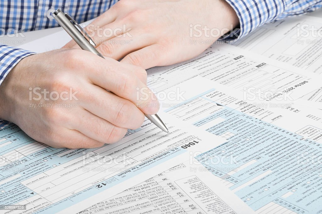 US Tax Form 1040 - man performing tax calculations stock photo