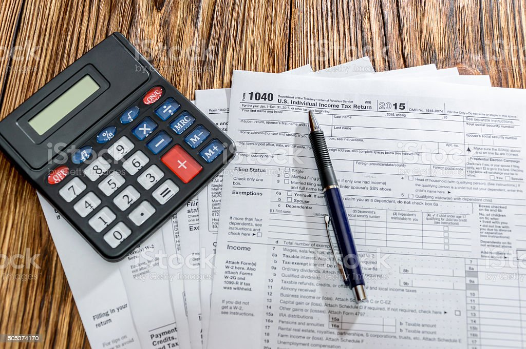 Tax form 1040 with pen and calculator on the table stock photo